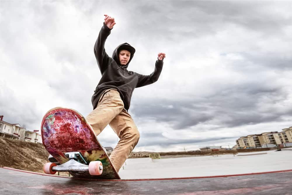 teen skater slides over a railing on a skateboard