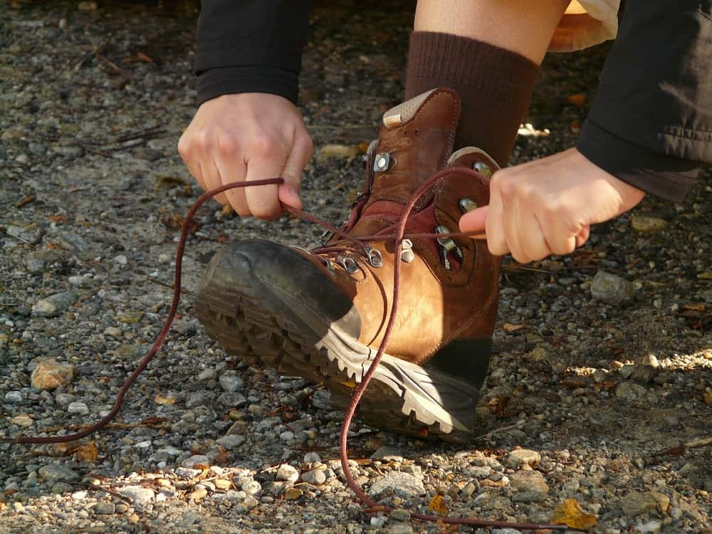 man tie shoe lace during hiking on trail