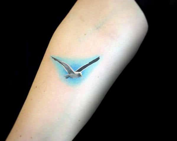 Tiny Mens Detailed Flying Seagull With Blue Sky Background Tattoo Inspiration On Arm