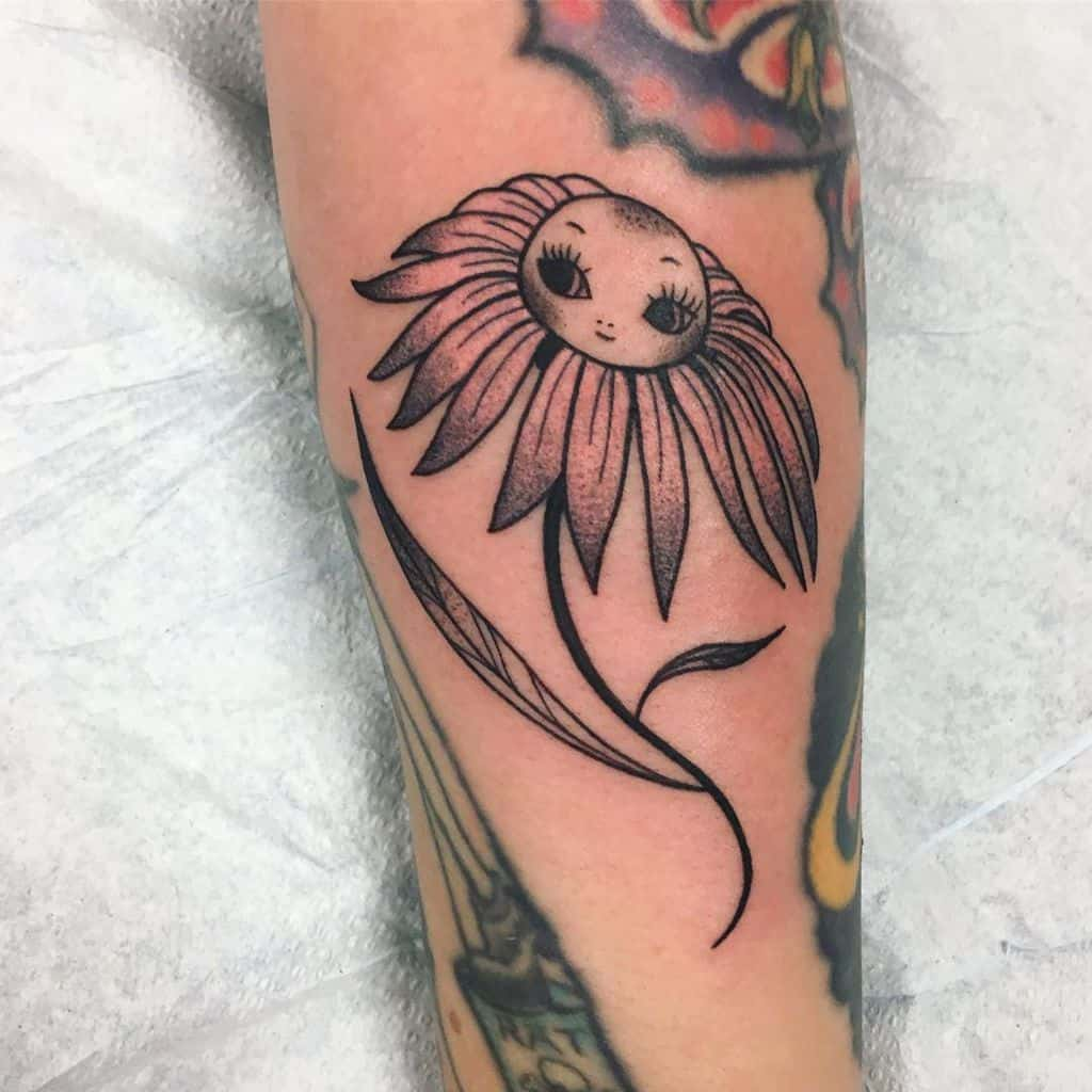 Forearm tattoo traditional color daisy with a cartoon face