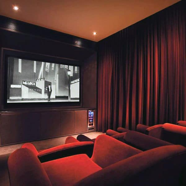 traditional home theater design with red seating and curtains