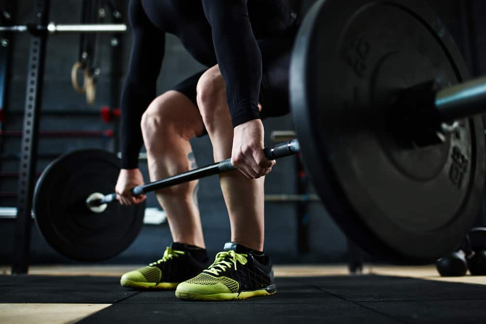 training barbell wearing green and black shoe