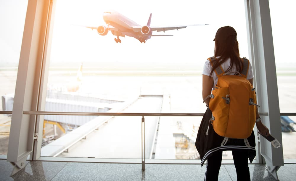 traveler woman with backpack see airplane flight at the airport