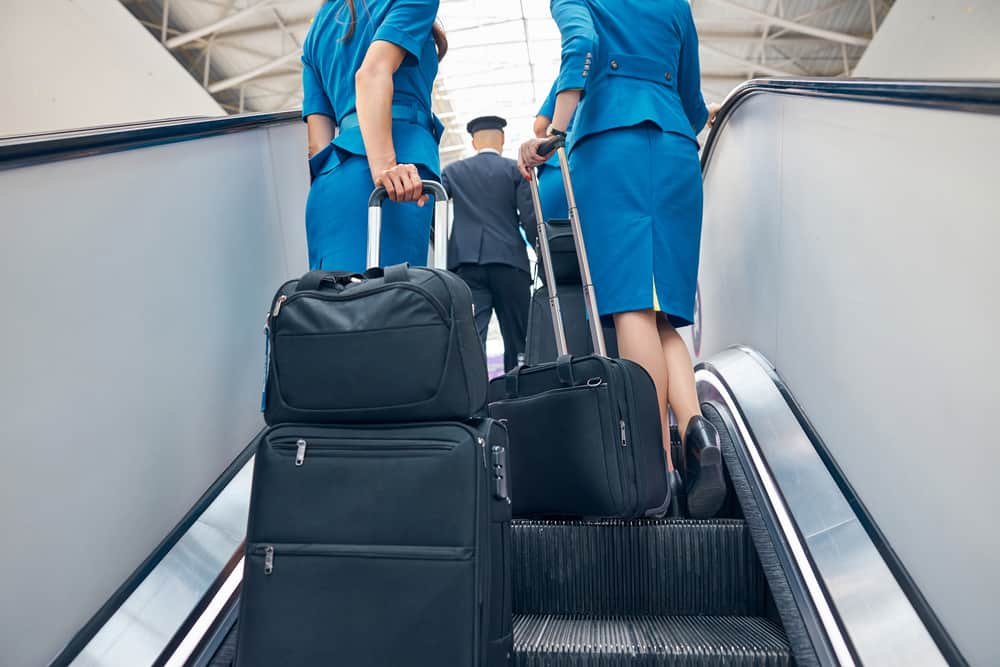 flight attendants and pilot with trolley luggage bags