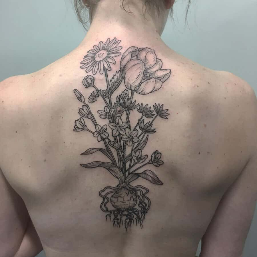 Center back tattoo large black and grey tulips and daisies with roots