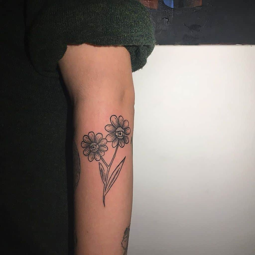 Forearm tattoo black and grey shading two daisies with eyes