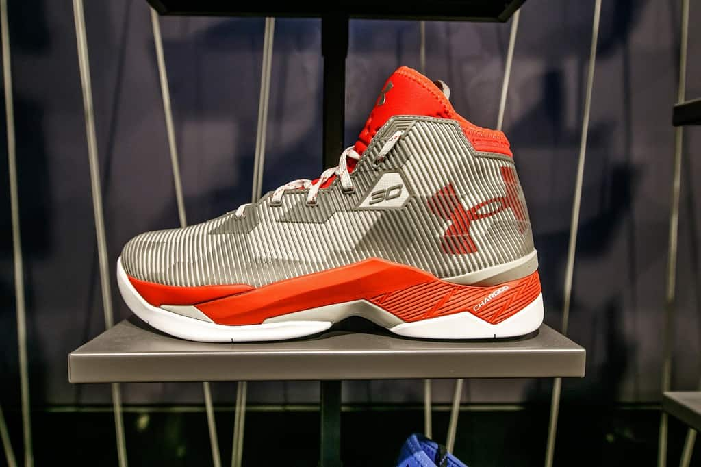 An orange and grey Under Armour basketball shoe.