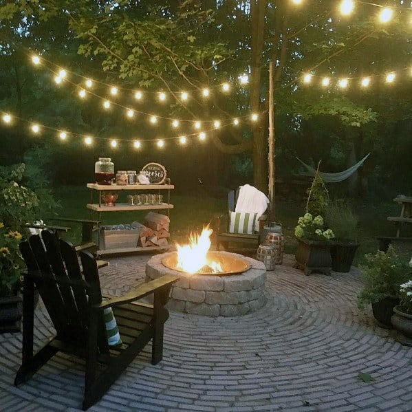 Unique Brick Patio Fire Pit With Circular Pattern And String Lights