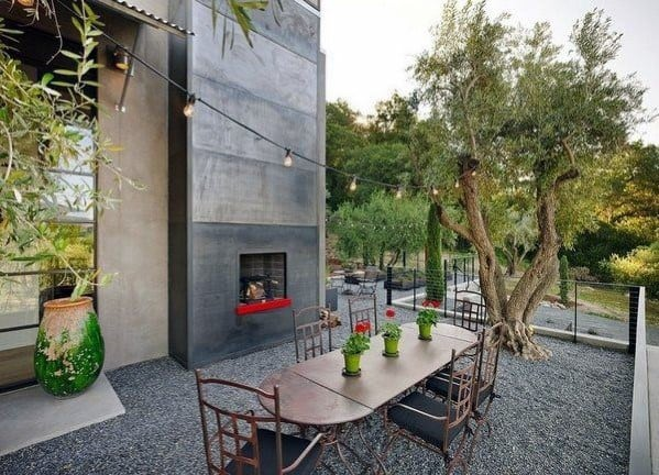 Unique Gravel Patio Backyard With Tall Fireplace
