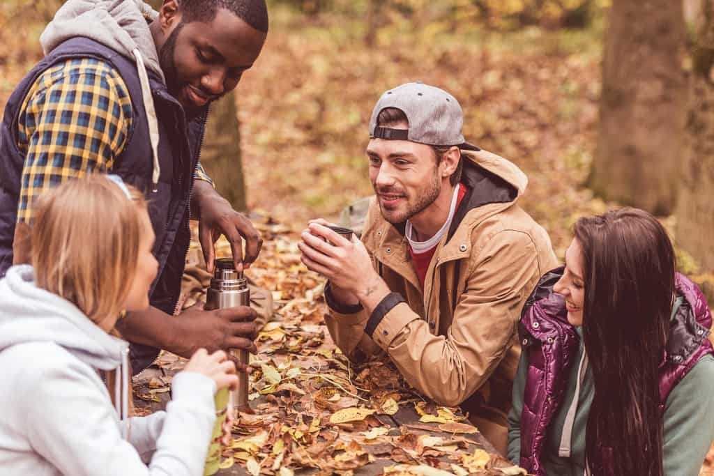 group of friends drinking hot water from a thermos at a picnic bench in autumn