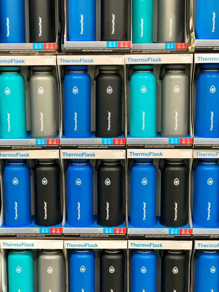 large shelf holding blue and black Thermoflask vacuum sealed bottles with company logo