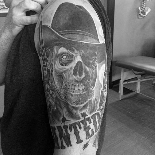 Wanted Black And Grey Skull Western Bicep Tattoo On Man