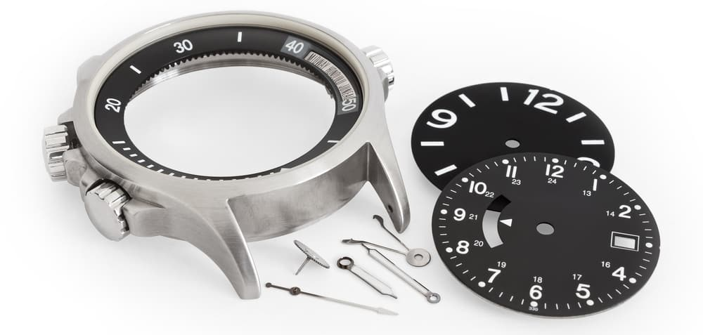 different watch parts laying on white background