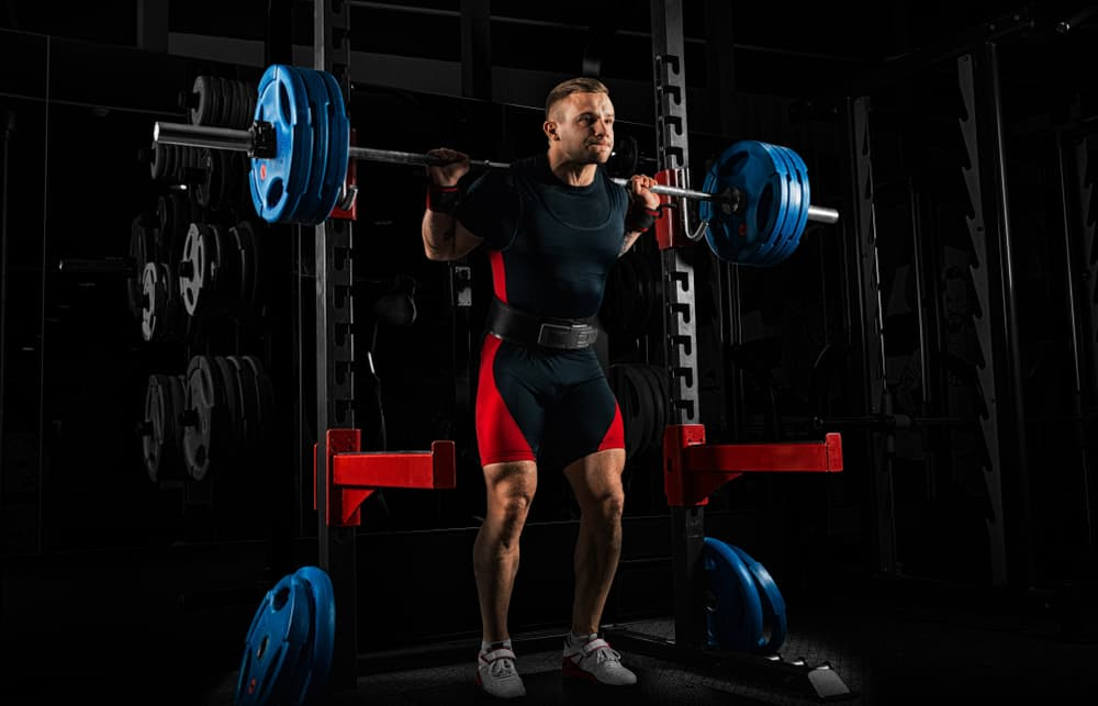 weightlifter stands with a very heavy barbell on his shoulders