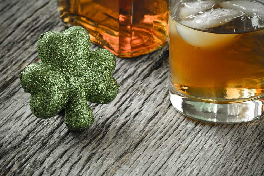glass of whiskey and clovers for celebration