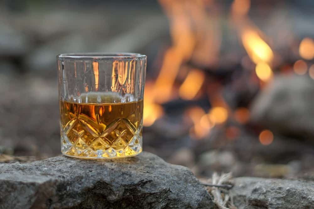 half filled whiskey glass near to fire