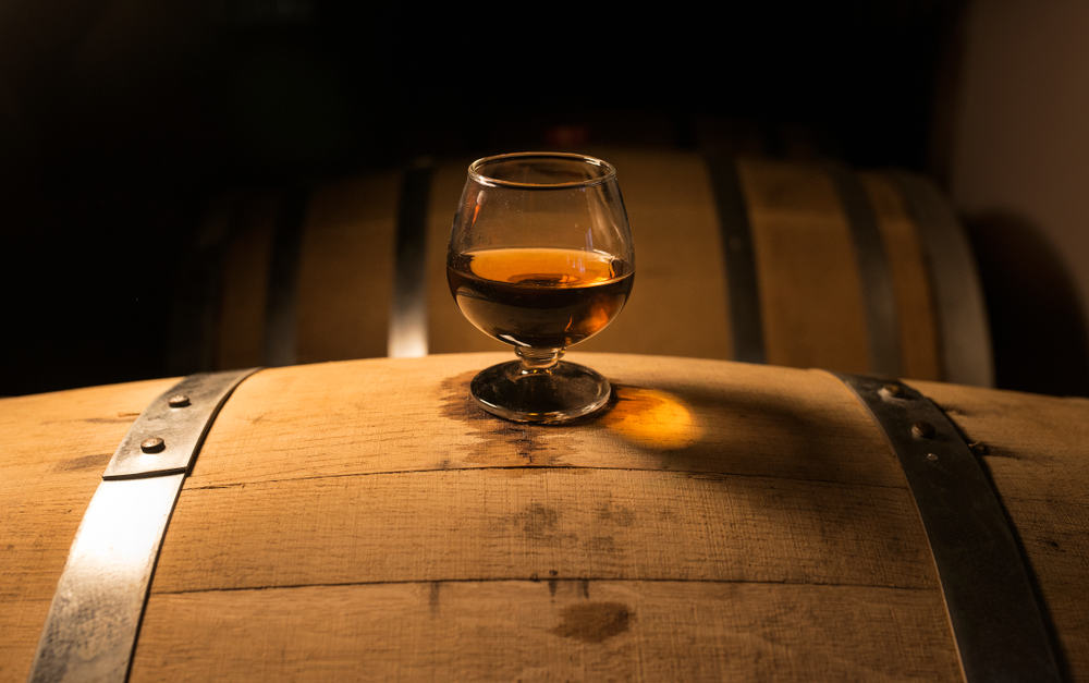 whiskey glass sits atop of whiskey barrel