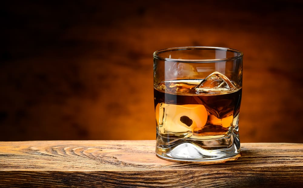 whiskey glass with ice on wooden table