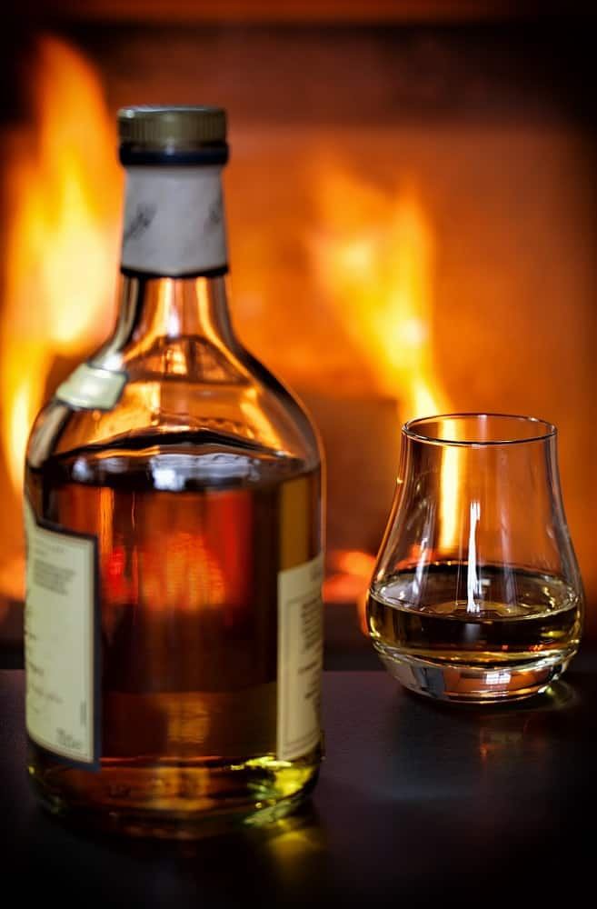 whisky bottle with glass near fire