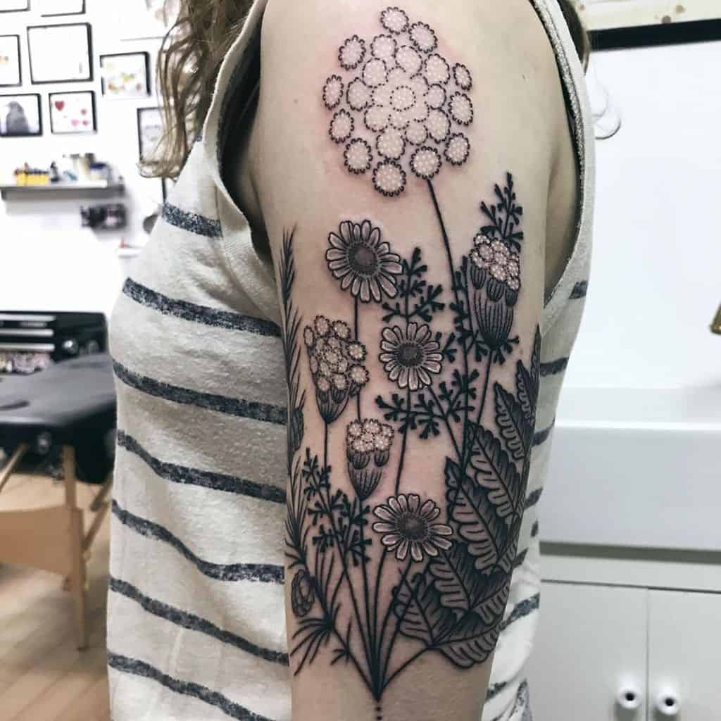 Upper arm tattoo large black and grey and white queen's lace pine cone fern and daisy