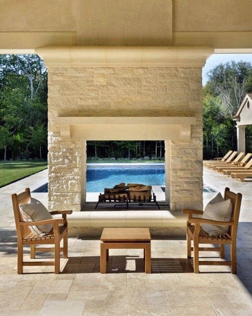 White Stone Outdoor Fireplace Next To Large Luxury Pool
