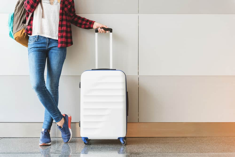 young women traveler at airport posing with white travel bag