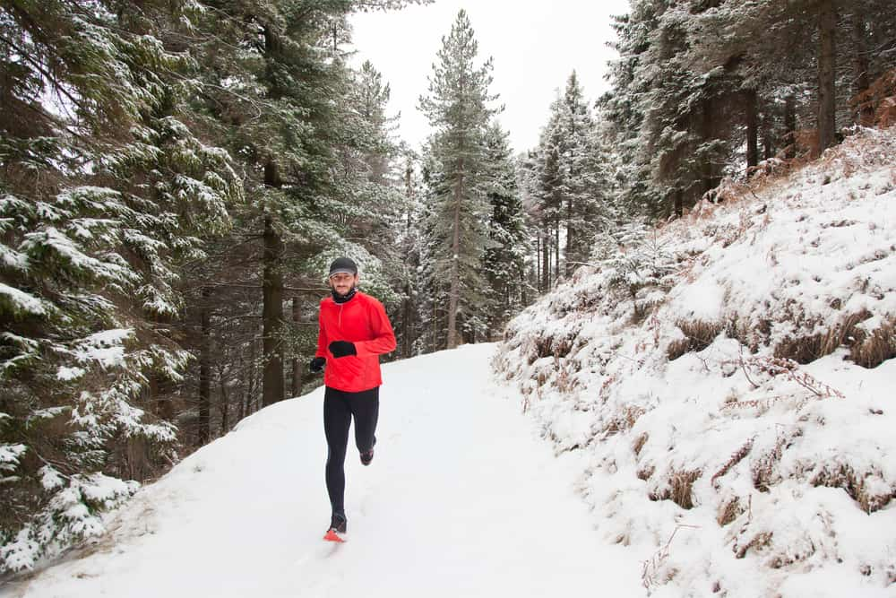athlete running on trail during winter