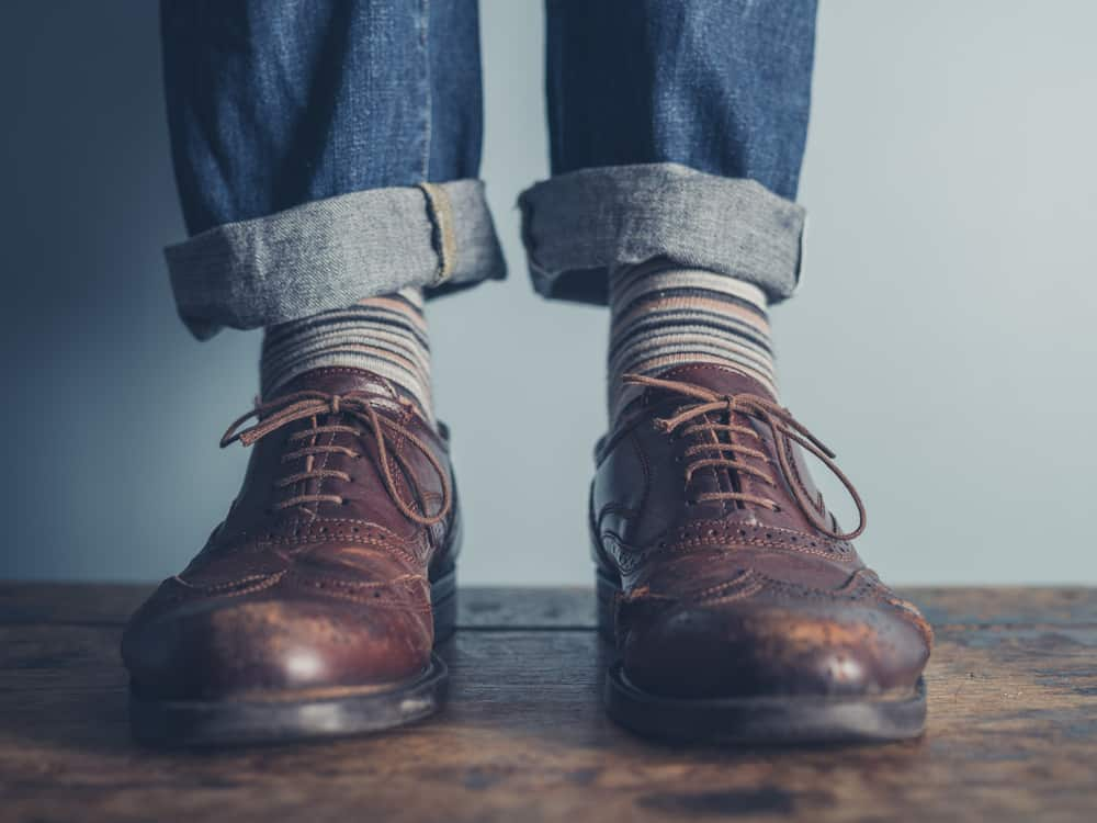 The feet of someone wearing a worn-in pair of brogues and cuffed jeans
