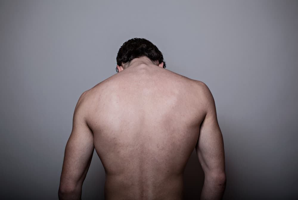 young man back isolated on gray background