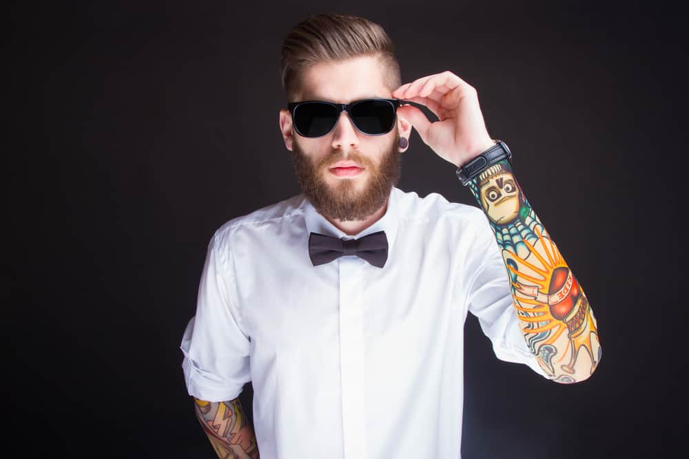 A young man with sleeve tattoos wearing sunglasses and a bow tie