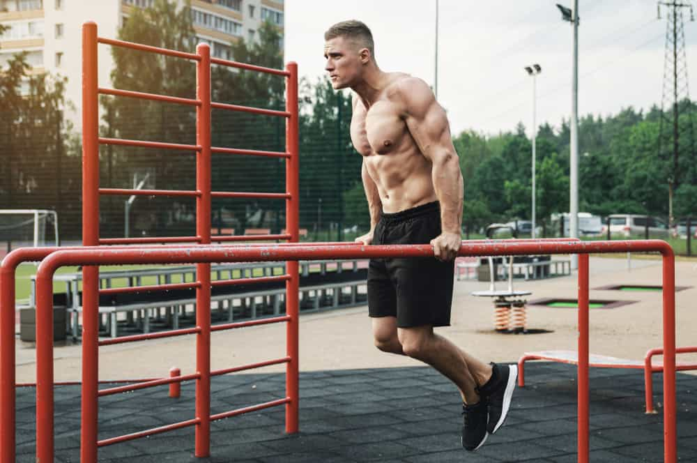 young muscular man doing parallel bar dip chest exercise