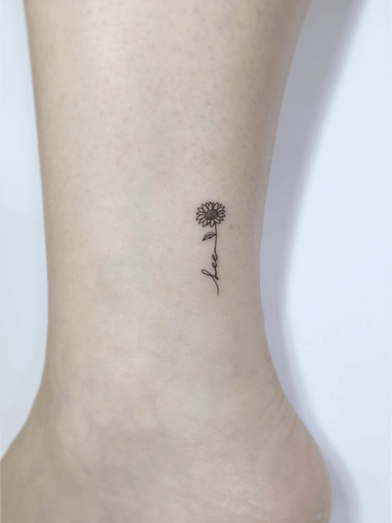 tiny black line tattoo on woman's ankle of a sunflower with the word love in its stem
