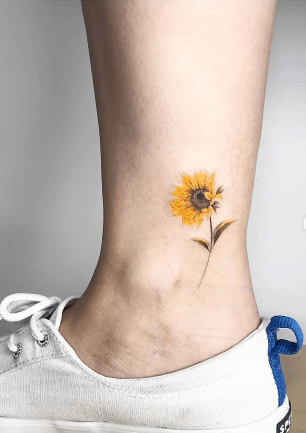 small color tattoo on woman's ankle of realistic sunflower with stem